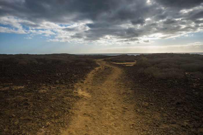 Path on the ground in the desert. Ocean at the end. Desert Freedom Peace Beauty In Nature Cloud - Sky Day Dry Climate Landscape Nature No People Outdoors Rock Object Scenics Silence Sky Solitude Tenerife Island The Way Forward Tranquil Scene Tranquility