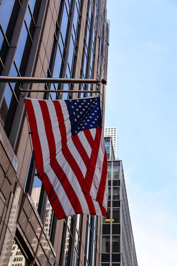 Low angle view of flag against buildings in city against sky