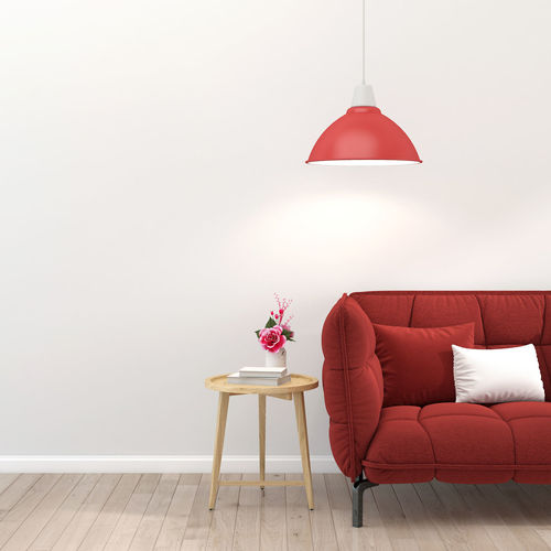 Red umbrella on table against wall at home