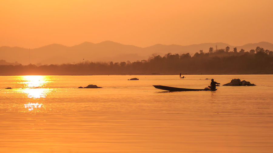Silhouette man sailing boat in river against orange sky during sunset