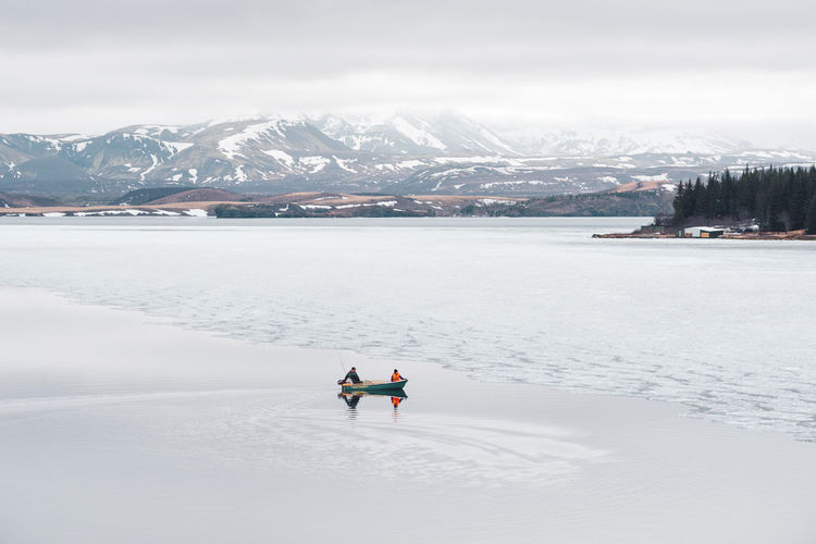 fishermen on boat against snowcovered mountain backdrop Ice Iceland Mountain View Nature Photography Adventure Beauty In Nature Boat Cold Temperature Environment Fisherman Fisherman Boat Fishermen's Life Iceland Trip Icelandtrip Lake Lake View Landscape Leisure Activity Lifestyles Men Mountain Mountain Range Nature Outdoor Photography People Philipp Dase Real People Scenics - Nature Snow Snowcapped Mountain Tranquil Scene Tranquility Two People Warm Clothing White Color Winter