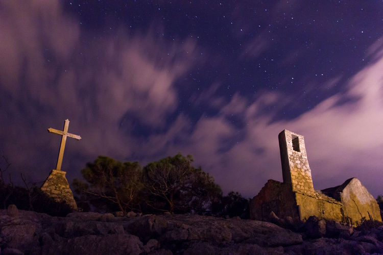 Cross on rock against sky at night