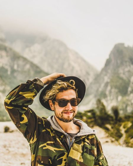 Portrait Of Man Wearing Sunglasses Against Mountains