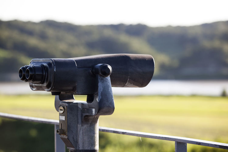 Close-Up Of Coin-Operated Binocular Against River