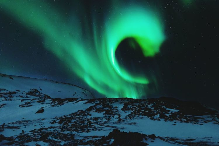 Scenic View Of Snowcapped Mountains Against Aurora Borealis In Sky