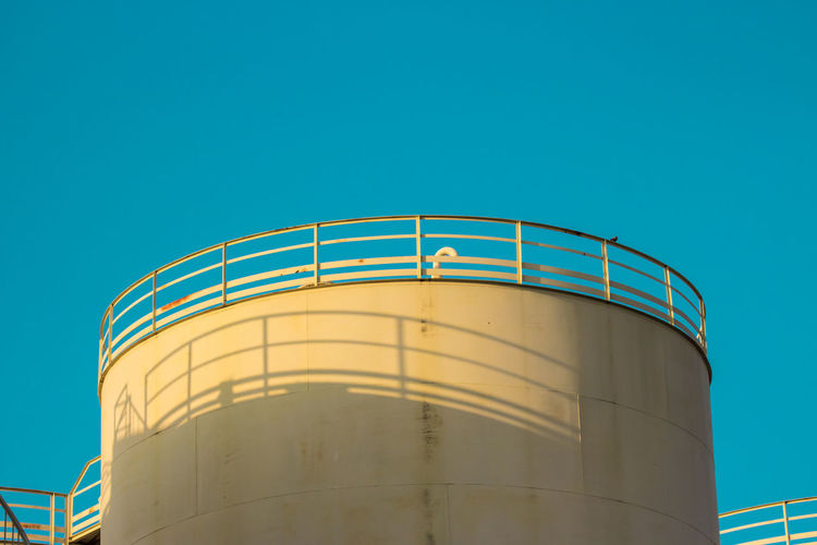 Low Angle View Fuel And Power Generation Storage Tank Copy Space Industry Architecture Sky No People Blue Clear Sky Silo Nature Built Structure Factory Container Storage Compartment Fuel Storage Tank Day Metal Oil Industry Outdoors