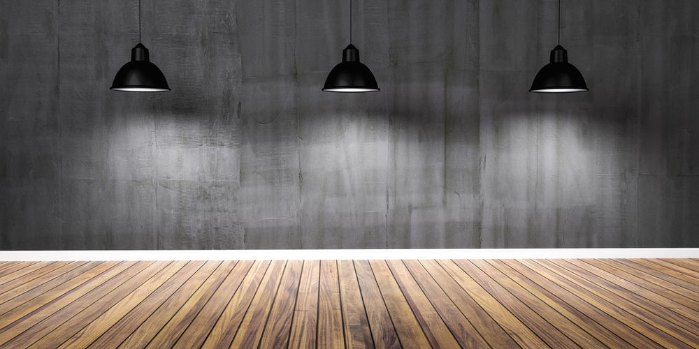 View of illuminated lamp on floor against wall