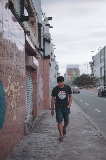 Full length of young man walking on street against buildings