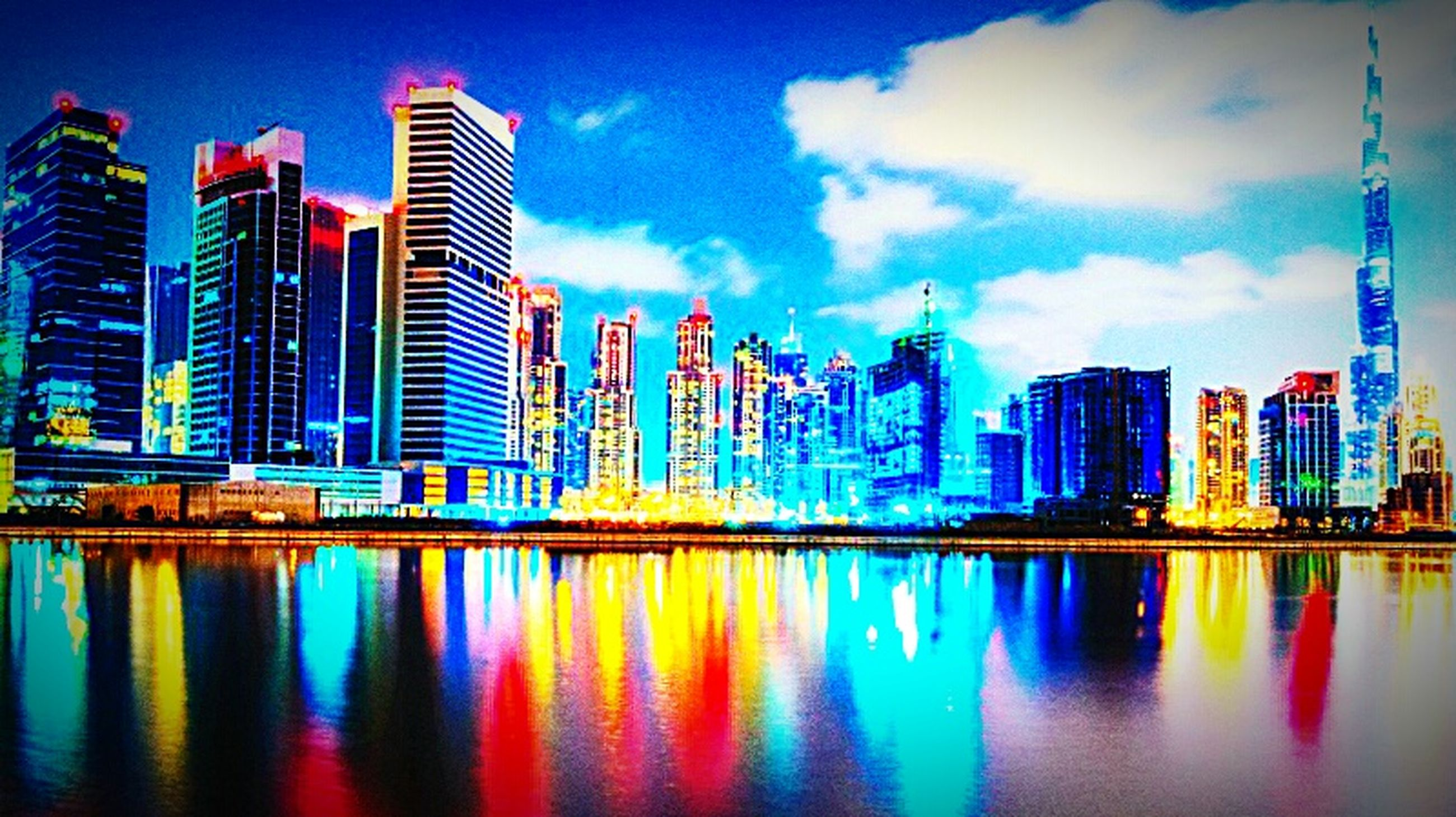 architecture, city, water, building exterior, waterfront, built structure, reflection, sky, skyscraper, multi colored, tall, building story, blue, tall - high, cityscape, river, growth, modern, illuminated, tower, urban skyline, calm, cloud, water surface, office building, sea, financial district, urban scene, city life, cloud - sky, tranquility, development