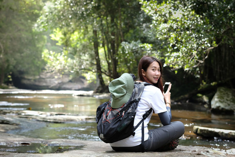 Portrait Of Young Woman Using Phone While Sitting At Riverbank