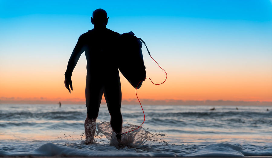 Rear view of man carrying equipment while walking in sea against sky during sunset