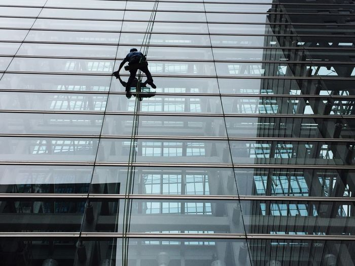 Low angle view of man cleaning glass building