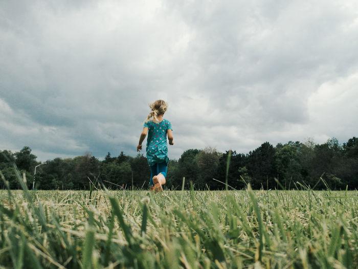 Cute little girl run on meadow. kids girl legs feet in rain boots. freedom innocence and adolescense