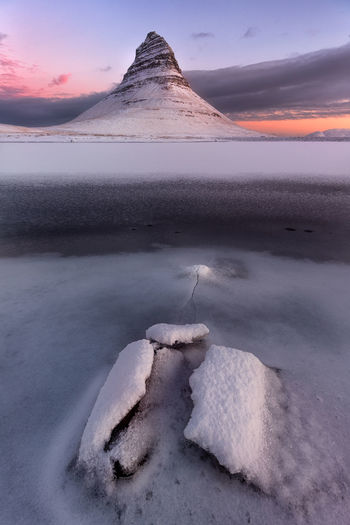 The majestic Kirkjufell, arguably the most iconic landmark of Iceland, really shines under first rays of sunrise. Iceland Kirkjufell Winter Arctic Crack Of Ice Cracked Europe Frozen Ice Lake Landscape Mountain Nature No People North Outdoors Remote Scenics Sky Snow Sunrise Tranquil Scene Tranquility Water Winter