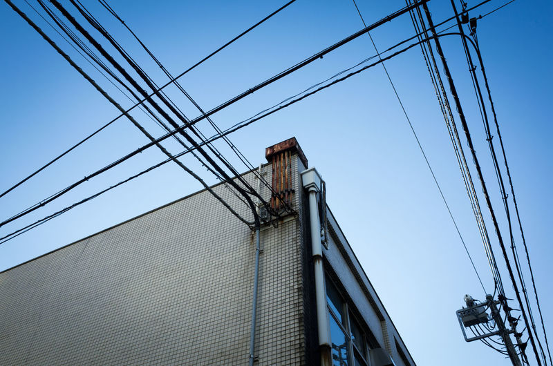 Low angle view of power cables on building