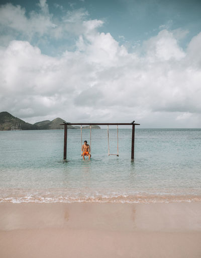 Man sitting on swing at beach against sky