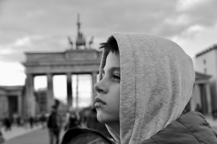 Close-up of thoughtful boy looking away against sky in city