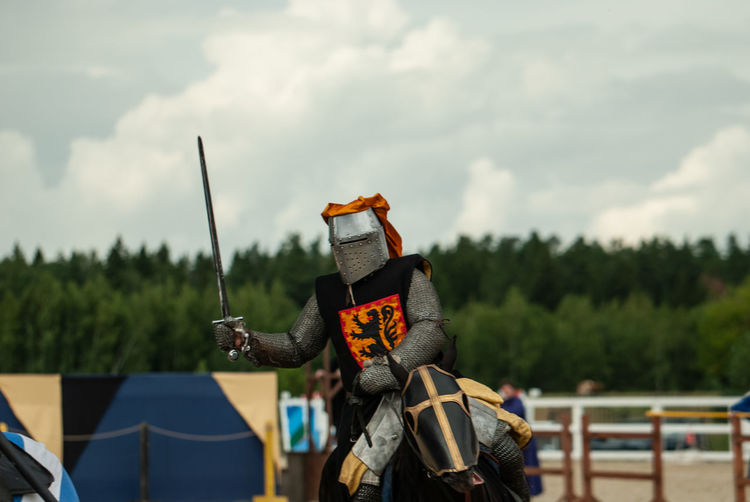 Knight holding sword riding on horse