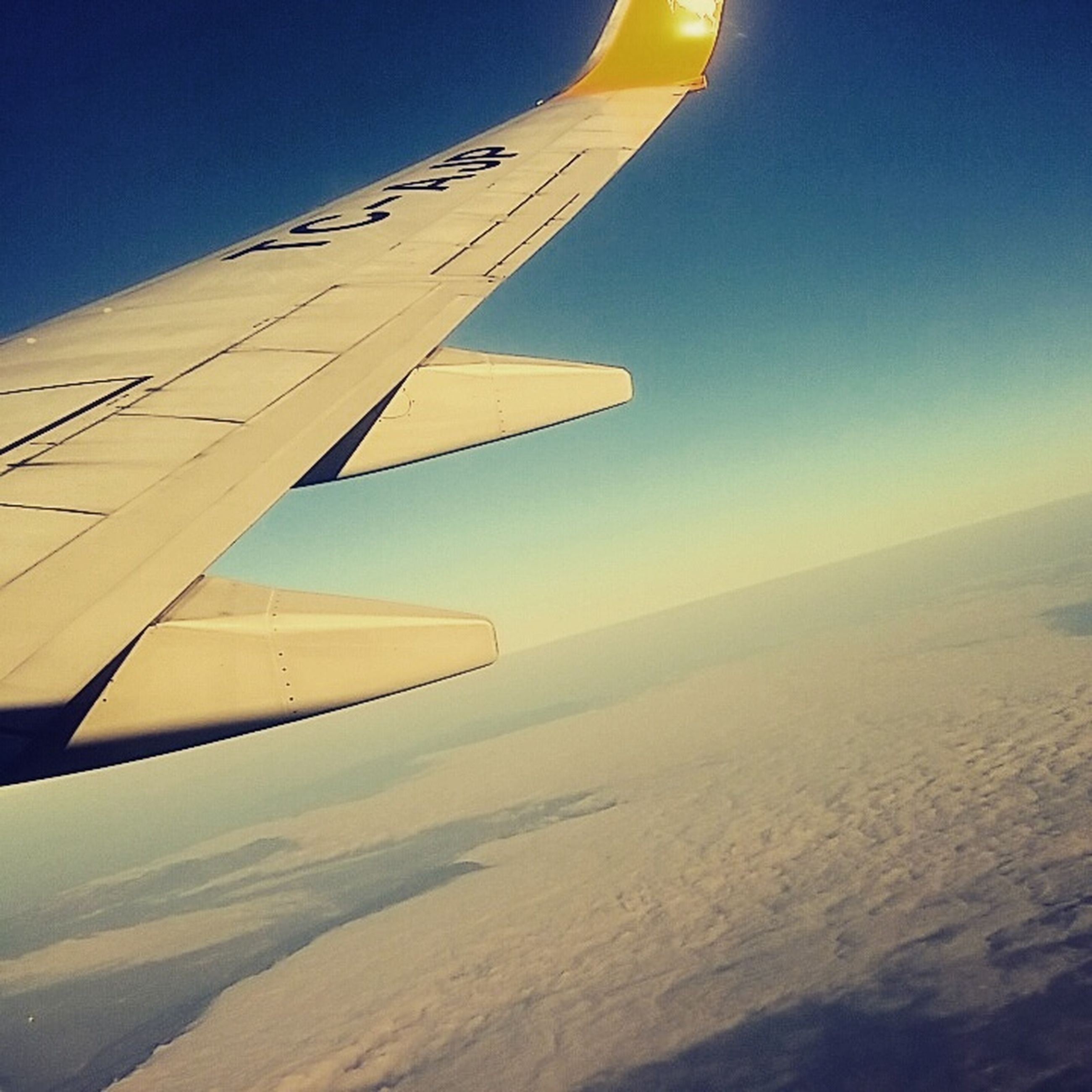 transportation, aircraft wing, mode of transport, air vehicle, part of, cropped, journey, aerial view, public transportation, landscape, on the move, mid-air, vehicle part, sky, scenics, sunset, beauty in nature, nature, blue, outdoors, no people, tranquility, tranquil scene, horizon over land, idyllic