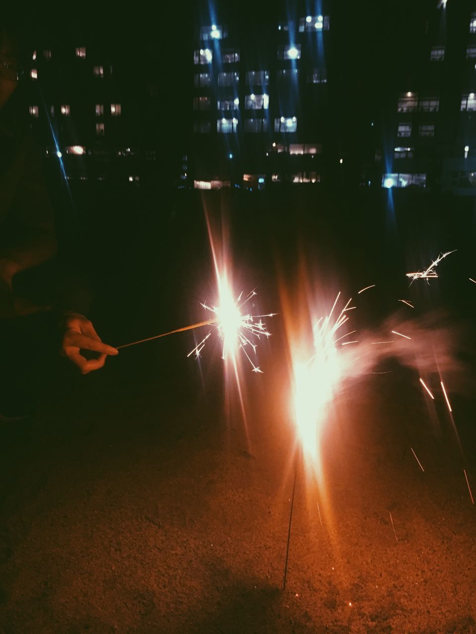 night, illuminated, motion, blurred motion, long exposure, real people, one person, glowing, burning, human hand, sparks, hand, firework, nature, flame, building exterior, men, heat - temperature, holding, architecture, sparkler, firework - man made object, lens flare