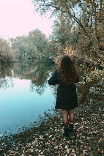 Rear view of woman standing by lake
