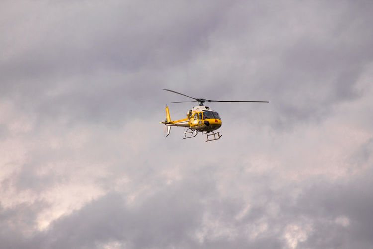 Low angle view of yellow helicopter against sky