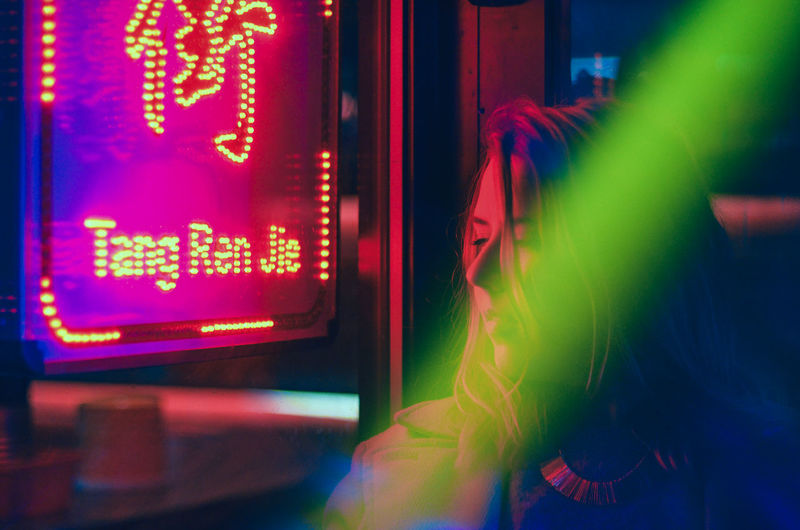 Close-up of young woman by illuminated neon sign at night