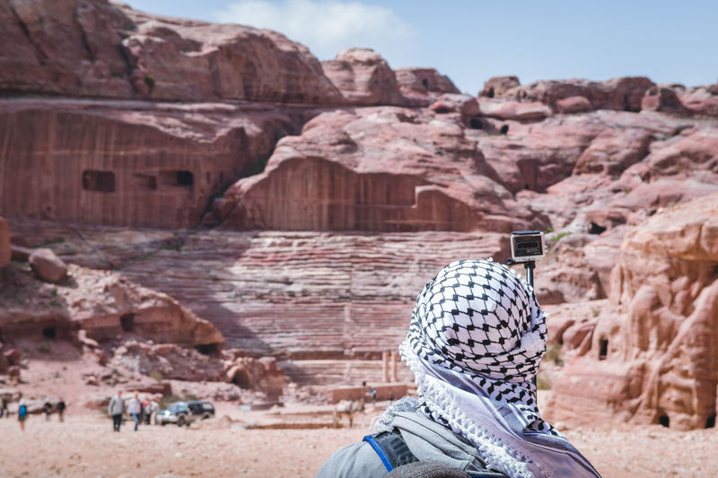 Rear view of woman taking selfie with camera wile standing against rock formation