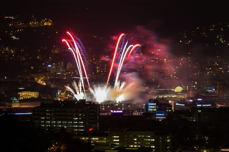 Firework display over city at night