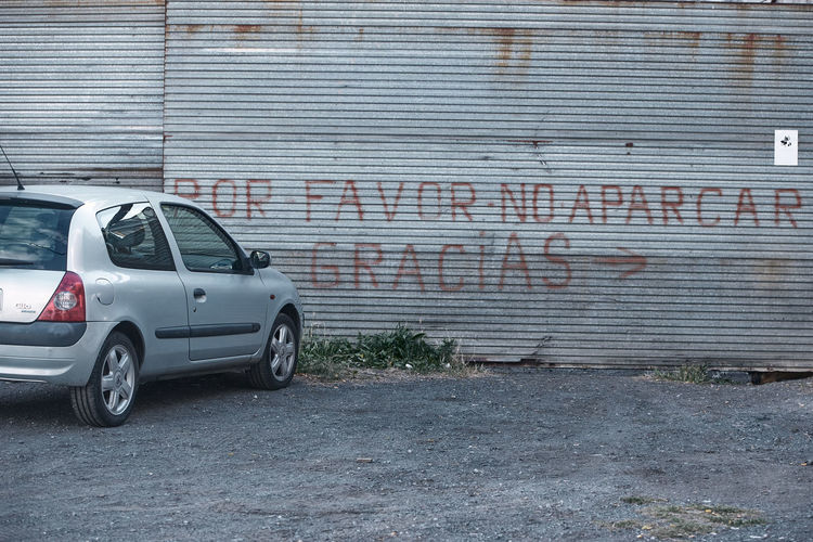 Cars on street against wall