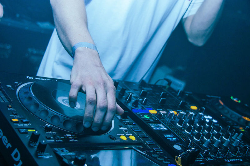 Midsection of man spinning decks  at underground rave