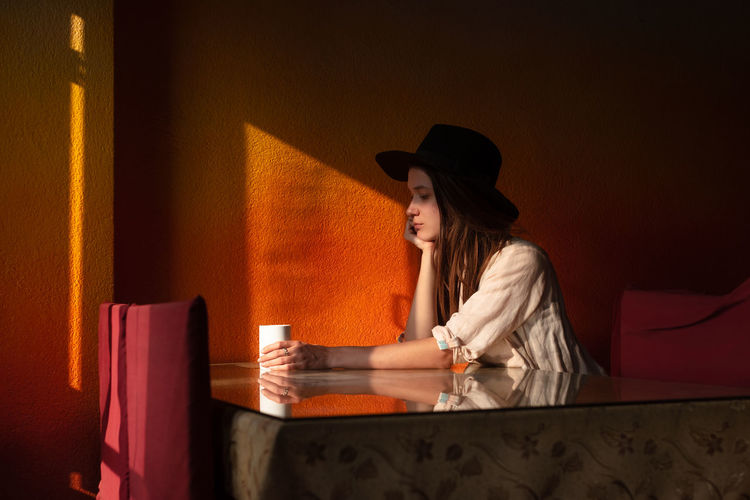 Woman sitting on table against wall