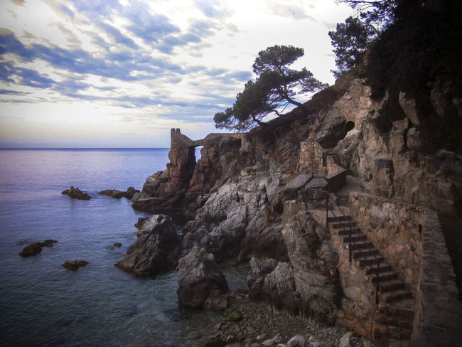 Rocks at Dawn, Lloret de Mar is a Mediterranean coastal town in Catalonia, Spain. One of the most popular holiday resorts on the Costa Brava Lloret De Mar Beauty In Nature Catalonia Cliff Cloud - Sky Geology Horizon Over Water Mediterranean  Mediterranean Seascape Nature Rock - Object Rock Formation Rocks And Water Scenics Sea Shore Sky SPAIN Stone - Object Tranquil Scene Tranquility Travel Travel Destinations Vivid International Water