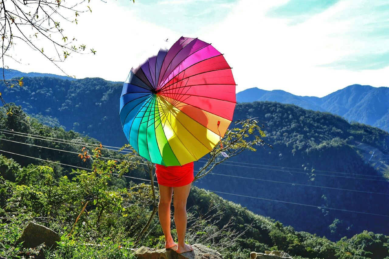 Rear View Of Woman With Colorful Umbrella Standing On Mountain Against Sky