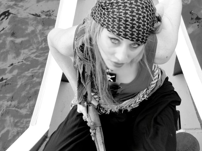 High Angle Portrait Of Woman In Pirate Costume Sitting On Boat Over Rivers