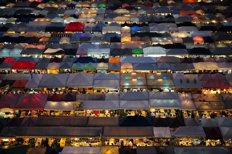High angle view of people in illuminated market at night