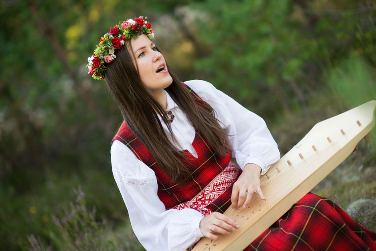 Nature Beautiful Woman Beauty Beauty In Nature Concert Day Flower Flower Wreath Girl Harp Leisure Activity Lifestyles Lute Musical Instrument National Costume Nature One Person Outdoors People Real People Red Smiling String Instrument Young Adult Young Women