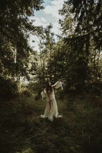 Woman standing on land against trees in forest