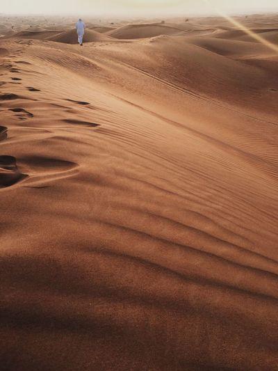 Surface level of sand dunes in desert against the sky