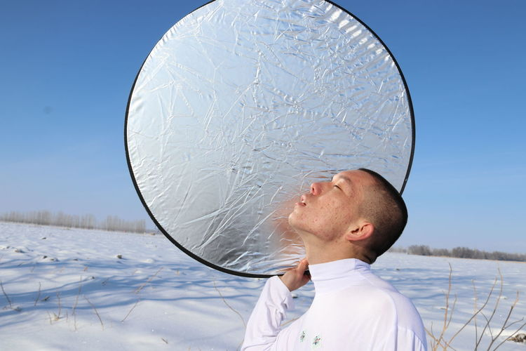 Young man with foil against clear sky during winter