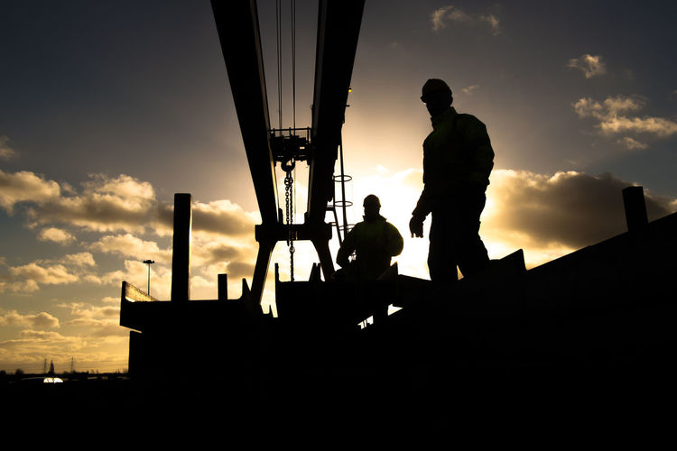 Silhouette Workers By Metallic Structure Against Cloudy Sky During Sunset