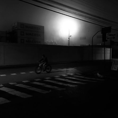Man riding bicycle on road at night