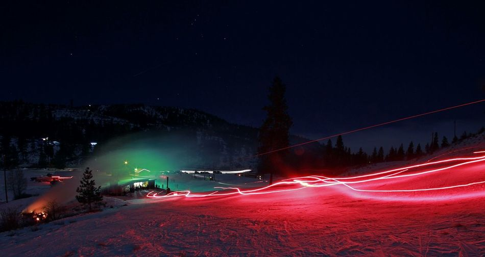 Light trails on snow covered mountains at night