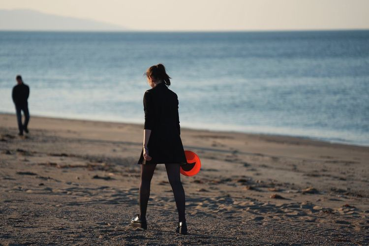 a young woman in black outfit walking on a beach at the sea holding frisbee in her hand Short Skirt  Recreation  Summer Vacation Red Frisbee Frisbee Beach Land Sea Water Horizon Over Water Sky Horizon Leisure Activity Full Length Sand Real People Nature Scenics - Nature Beauty In Nature Lifestyles Women Walking Outdoors International Women's Day 2019