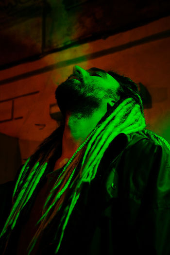 Bearded man with synthetic dreadlocks in green and red neon light smoking a cigarette and puffing clouds of smoke One Person Portrait Headshot Lifestyles Real People Young Adult Smoking Dreadlocks Dreadhead Smoking Weed Smoking - Activity Man Kanekalon Beardlife Smoker Neon Lights Neon Colored Light And Shadow Street Light Street Style from Around The World Brutalism Green Color Dark Night Nightlife