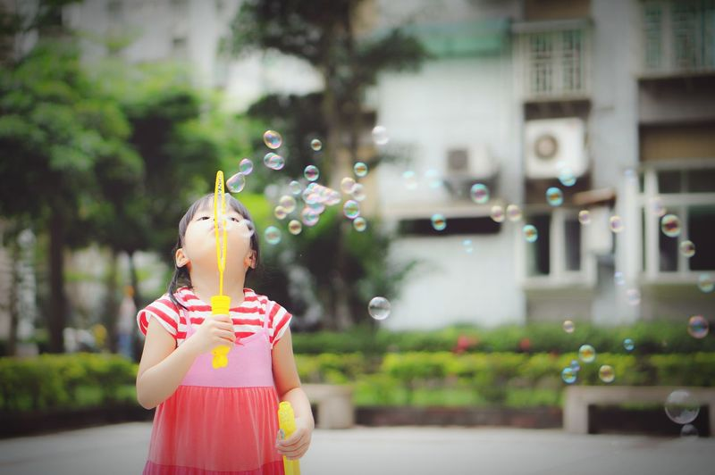 Girl playing with bubble wand
