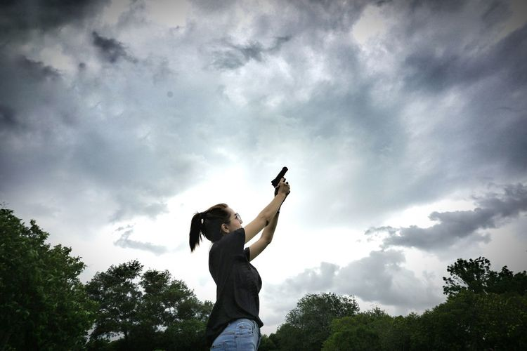 Low Angle View Of Woman Aiming With Gun Towards Stormy Clouds