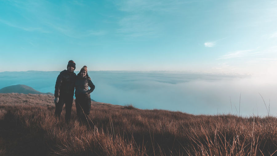 Couple standing on cliff against cloudy sky