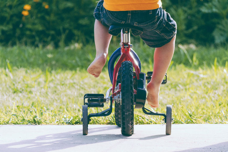 Low section of boy riding bicycle on road