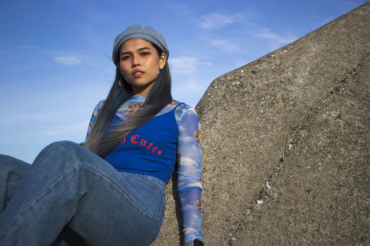 Low angle view of young woman sitting against blue sky